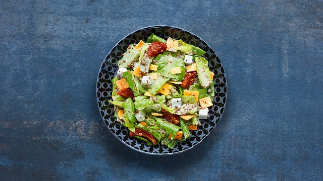A bowl filled with salad, tomatoes and pitta croutons.